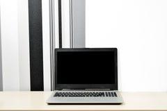 嘲笑膝上型计算机,在书桌上的笔记本在minimalistic黑白背景墙壁上 库存照片