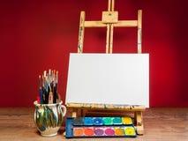 嘲笑画架调色板水彩和刷子与空的白色帆布 免版税图库摄影