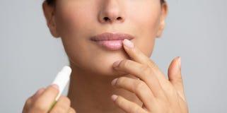 嘴唇皮肤护理 应用凤仙花的蓬松卷发妇女 免版税库存照片