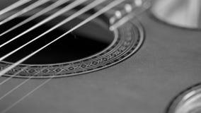 嘴的特写镜头画象和一把声学吉他的串 免版税库存图片
