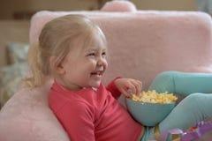 嘻嘻笑在她在电视观看的事的小女孩 库存图片