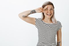 嘿水手 有公平的头发的,广泛地闪光和微笑与的迷人的嬉戏的在胳膊的女孩和纹身花刺画象 免版税库存照片