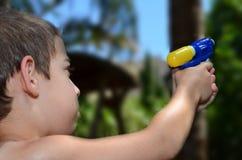 嘿!一个年轻男孩严肃对他的水玩具枪 免版税库存照片