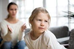 噘嘴阴沉的恼怒的被触犯的孩子的女孩忽略责骂h的母亲 库存照片