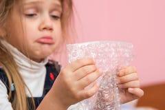 噘嘴面颊的生气女孩吃包装影片的泡影 免版税图库摄影