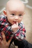 嚼在手指的秃头男婴 免版税库存照片