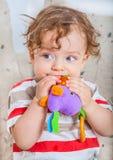 嚼在玩具的男婴 免版税库存照片