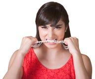 嚼在项链的沮丧的妇女 免版税图库摄影