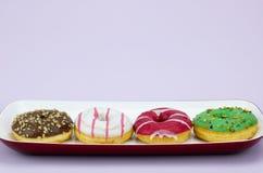 四上色了在淡紫色背景隔绝的盘子的油炸圈饼 免版税库存图片