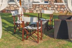 四与一张桌的木椅子在绿草的庭院里 库存图片
