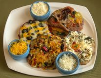 四个不同微型薄饼和三个小碗用搓碎干酪 免版税库存图片