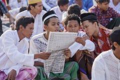 四个人在祈祷以后读了一张报纸 免版税库存照片
