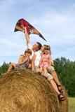愉快的家庭横跨干草飞行风筝。 库存图片