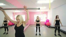 四个俏丽的女孩,参与体育,举在健身房的健身酒吧 体育生活和一种健康生活方式 影视素材