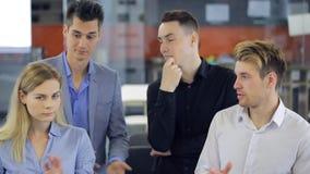 四个办公室工作者在会场里站立并且拍他们的手 股票录像
