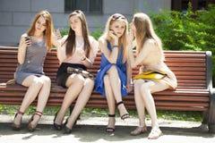 四个十几岁的女孩坐长凳在夏天公园 免版税图库摄影