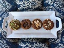 四个南瓜松饼在蓝色和白色的一个白色服务盘子仿造了背景 库存照片