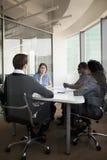 四个商人坐在会议桌上和谈论在业务会议期间 库存图片