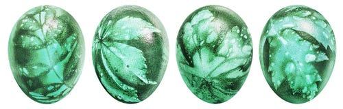 四个复活节彩蛋的汇集洗染了鲜绿色和装饰用杂草在白色背景隔绝的叶子版本记录 库存照片