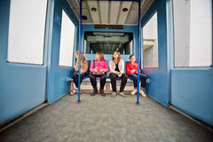 四个女孩在单轨铁路车火车支架坐  库存图片
