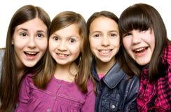 四个女孩愉快的微笑的年轻人 免版税库存图片