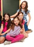 四个学校女孩和黑板 免版税库存照片