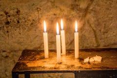 四个安静的蜡烛,闪烁在一间偏僻的屋子 库存图片