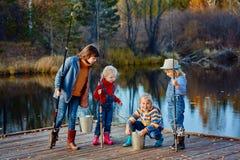 四个小女孩抓在一艘木浮船的鱼 在湖的周末 钓鱼与朋友 图库摄影