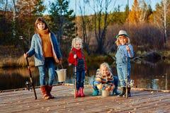 四个小女孩抓在一艘木浮船的鱼 在湖的周末 钓鱼与朋友 免版税库存图片