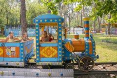 四个小孩在children& x27乘坐; s火车在公园 免版税库存照片