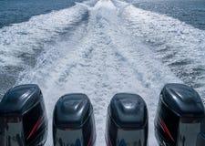 四个小船马达在水留下泡沫通行证  图库摄影