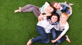 四个少妇坐绿草 库存图片