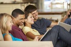 四个少年在家坐沙发使用片剂计算机和膝上型计算机,看电视 免版税库存图片