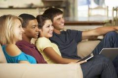 四个少年在家坐沙发使用片剂计算机和膝上型计算机,看电视 免版税图库摄影