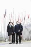 四个微笑的年轻商人常设外部,飞行在背景中的旗子 免版税库存照片