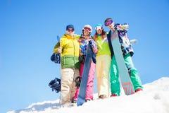 四个愉快的朋友拥抱和举行雪板 库存图片