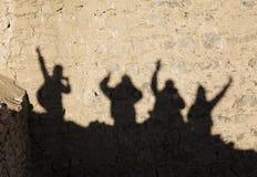 四个愉快的游人的阴影在Shey宫殿墙壁上的 图库摄影