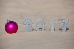 四个新年` s形象在海滩的沙子或海边,投下了在地面上的大阴影 在沙子附近是桃红色球 免版税库存图片