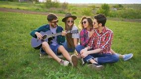 四个朋友拥抱,戏剧吉他并且唱歌曲户外在日落 影视素材