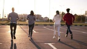 四个朋友由空的停车区户外负责-乐趣幸福、年轻人和妇女在晚上跑 股票录像