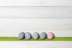 四个灰色和一个桃红色五颜六色的复活节彩蛋手工制造立场连续在以木表面为背景的绿色草坪与 图库摄影