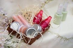 四个瓶子奶油,两支唇膏,两在一个明亮的瓶子的唇膏 免版税库存照片