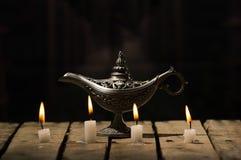 四个白色蜡蜡烛坐木表面燃烧, Aladin被安置的样式灯后边,黑背景 免版税库存照片