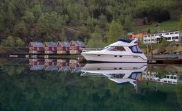 四个红色小屋和一条小船在港口在Flam村庄 免版税库存照片