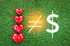 四个红色心脏和金钱标志在绿草调遣爱conce 免版税库存照片