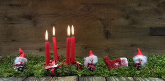 四个红色灼烧的出现蜡烛 与小的圣诞节背景 库存图片