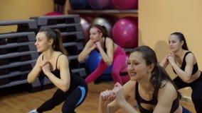 四个美丽的体育女孩在健身房蹲 股票录像