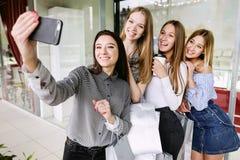 四个美丽的女孩在购物中心的做selfie 免版税库存照片