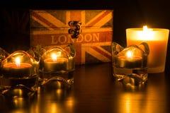 四个蜡烛和伦敦箱子在一个黑框架 免版税库存照片