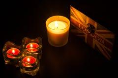 四个蜡烛和伦敦箱子在一个黑框架 免版税图库摄影
